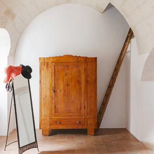 Imagen de armario y vestidor mediterráneo con suelo de baldosas de terracota