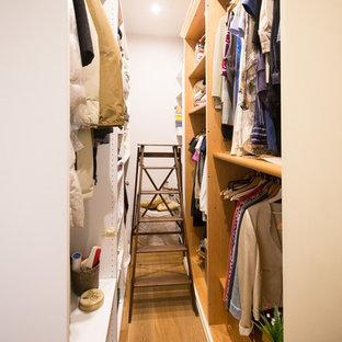 Foto di una piccola cabina armadio per donna stile shabby con nessun'anta, ante bianche, parquet chiaro e pavimento marrone