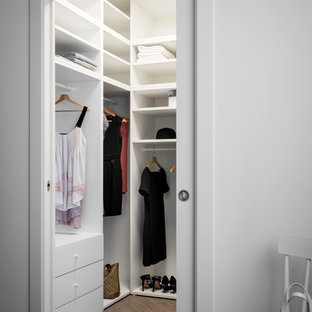 This is an example of a small contemporary gender-neutral walk-in wardrobe in Milan with open cabinets, white cabinets, porcelain floors and grey floor.