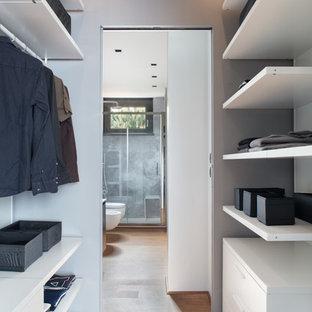 Esempio di una cabina armadio per uomo contemporanea con nessun'anta, ante bianche e pavimento in legno massello medio