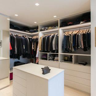 Esempio di un grande spazio per vestirsi unisex design con ante lisce, ante bianche, parquet chiaro e pavimento beige