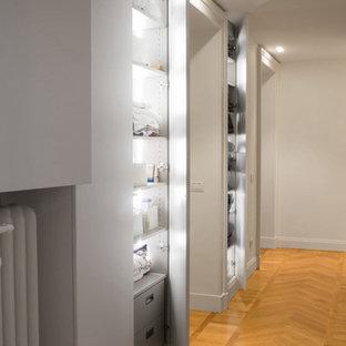 Idee per un piccolo armadio o armadio a muro unisex design con ante lisce, ante bianche e pavimento in legno massello medio