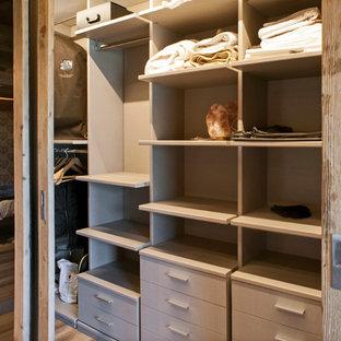 Diseño de armario unisex, rural, de tamaño medio, con suelo de madera clara, armarios estilo shaker y puertas de armario de madera oscura