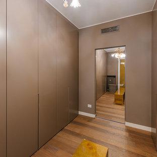 Idee per un grande spazio per vestirsi unisex contemporaneo con ante lisce, ante marroni e pavimento in legno massello medio