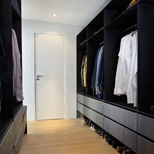 Imagen de armario vestidor de hombre, actual, con armarios con paneles lisos, puertas de armario negras, suelo de madera clara y suelo beige
