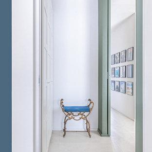 Foto de armario unisex, contemporáneo, de tamaño medio, con armarios con paneles empotrados, puertas de armario blancas, suelo de baldosas de porcelana y suelo beige