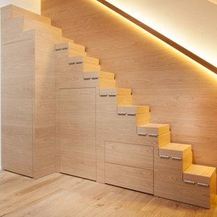 Exemple d'un placard dressing moderne de taille moyenne et neutre avec un placard à porte plane, des portes de placard en bois clair, un sol en bois brun, un sol marron et un plafond en bois.