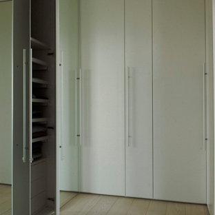 Foto di un'ampia cabina armadio unisex moderna con ante lisce, ante bianche, parquet chiaro e pavimento bianco