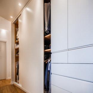 Esempio di un armadio o armadio a muro unisex minimal di medie dimensioni con ante lisce, ante bianche, pavimento in legno massello medio e pavimento marrone