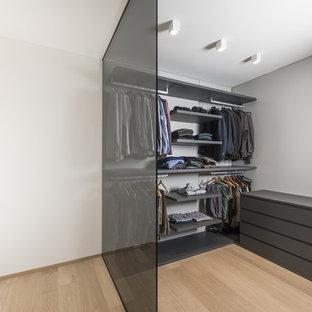 Imagen de vestidor de hombre, actual, de tamaño medio, con armarios abiertos, puertas de armario negras y suelo de madera clara