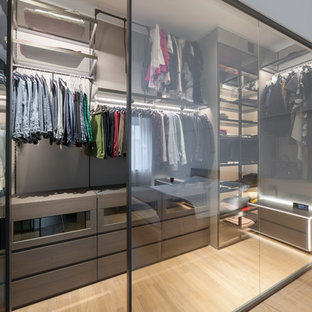 This is an example of a mid-sized contemporary gender-neutral walk-in wardrobe in Milan with flat-panel cabinets, brown cabinets, light hardwood floors and beige floor.