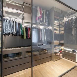 Réalisation d'un dressing design de taille moyenne et neutre avec un placard à porte plane, des portes de placard marrons, un sol en bois clair et un sol beige.