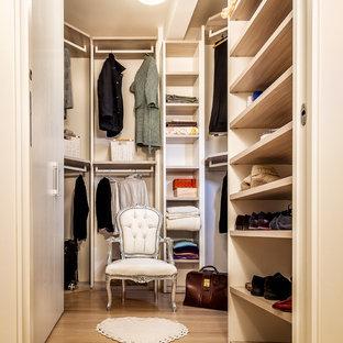 Foto di una cabina armadio unisex design di medie dimensioni con nessun'anta, ante beige, pavimento in laminato e pavimento marrone