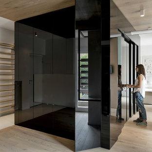 Modelo de armario vestidor unisex, contemporáneo, grande, con armarios con paneles lisos, puertas de armario negras y suelo de madera clara
