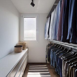 Ispirazione per una cabina armadio unisex design di medie dimensioni con ante lisce, ante grigie, pavimento in legno massello medio e pavimento marrone