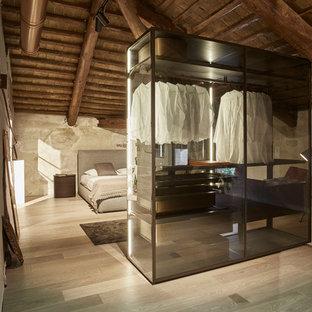 Ejemplo de armario vestidor unisex, rústico, con armarios tipo vitrina y suelo de madera clara