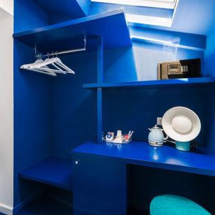 Esempio di un armadio incassato unisex moderno di medie dimensioni con ante lisce, ante blu, pavimento in gres porcellanato, pavimento grigio e travi a vista