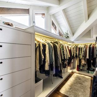 Idée de décoration pour un grand dressing tradition neutre avec un placard sans porte, des portes de placard blanches, un sol en bois brun et un sol marron.