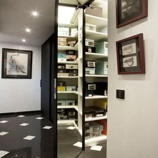 Foto di una cabina armadio per donna eclettica di medie dimensioni con ante di vetro, ante bianche, pavimento in marmo e pavimento nero
