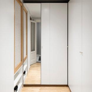 Idee per una cabina armadio unisex scandinava di medie dimensioni con ante lisce, ante bianche, parquet chiaro e soffitto ribassato