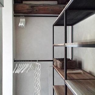 Ejemplo de armario vestidor unisex, rústico, con armarios abiertos, puertas de armario de madera oscura, suelo de cemento y suelo gris