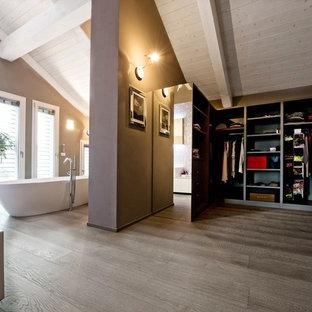 Foto di una cabina armadio unisex design con nessun'anta, ante grigie, pavimento in legno massello medio e pavimento marrone