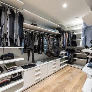 Ejemplo de armario vestidor unisex, minimalista, de tamaño medio, con armarios abiertos, puertas de armario blancas, suelo beige y suelo de madera clara
