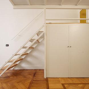 Imagen de armario unisex, industrial, pequeño, con armarios con paneles lisos, puertas de armario blancas, suelo de madera en tonos medios y suelo marrón