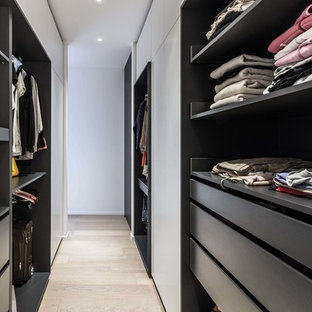 Idées déco pour un dressing contemporain de taille moyenne pour une femme avec un placard sans porte, un sol en bois clair et un sol jaune.