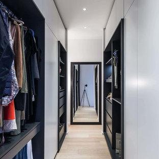 Ejemplo de armario vestidor de mujer, actual, de tamaño medio, con armarios abiertos, suelo de madera clara y suelo amarillo