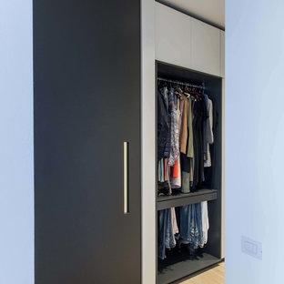 Modelo de armario vestidor de mujer, contemporáneo, de tamaño medio, con armarios abiertos, suelo de madera clara y suelo amarillo
