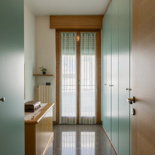 Inspiration for a small modern gender-neutral built-in wardrobe in Other with flat-panel cabinets, green cabinets, marble floors and black floor.