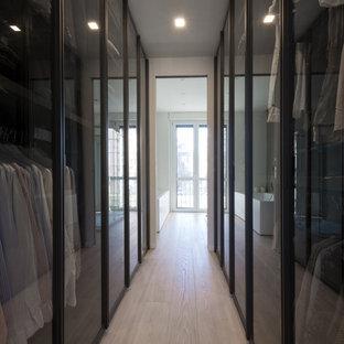 Modelo de armario vestidor unisex, contemporáneo, pequeño, con armarios tipo vitrina, puertas de armario marrones, suelo de madera clara y suelo beige