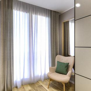 Foto di una cabina armadio unisex scandinava di medie dimensioni con ante lisce, ante beige, parquet chiaro e soffitto ribassato