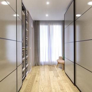 Ispirazione per una cabina armadio unisex nordica di medie dimensioni con ante lisce, ante beige, parquet chiaro e soffitto ribassato