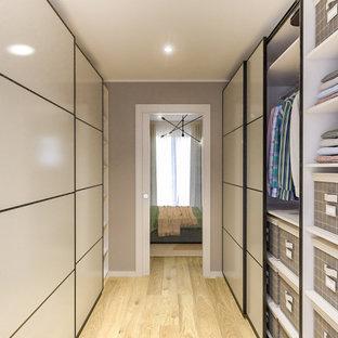 Inredning av ett minimalistiskt mellanstort walk-in-closet för könsneutrala, med släta luckor, beige skåp och ljust trägolv