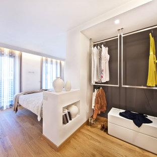 Esempio di piccoli armadi e cabine armadio unisex design con nessun'anta e pavimento in legno massello medio