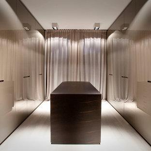 Foto de vestidor unisex, contemporáneo, extra grande, con armarios con paneles lisos, puertas de armario marrones y suelo de madera clara