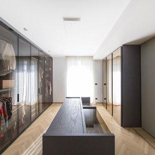 Ispirazione per uno spazio per vestirsi minimal con ante di vetro, parquet chiaro e pavimento beige