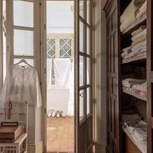 Foto de armario y vestidor romántico con suelo de baldosas de cerámica, puertas de armario de madera oscura y suelo rojo