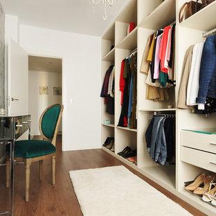 Diseño de armario y vestidor de mujer, tradicional renovado, con armarios con paneles lisos, puertas de armario beige, suelo de madera oscura y suelo marrón