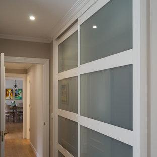 他の地域の中サイズの男女兼用エクレクティックスタイルのおしゃれなウォークインクローゼット (茶色い床、ガラス扉のキャビネット、白いキャビネット、ラミネートの床) の写真
