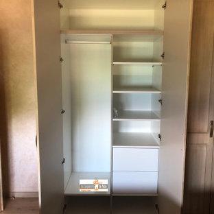 Exemple d'une armoire encastrée tendance de taille moyenne et neutre avec un placard à porte affleurante, des portes de placard en bois brun, un sol en carrelage de céramique, un sol beige et un plafond décaissé.