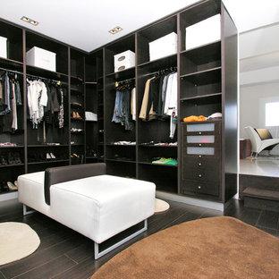 Ejemplo de vestidor unisex, actual, de tamaño medio, con armarios abiertos, puertas de armario negras, suelo marrón y suelo de madera oscura