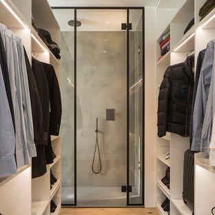 Foto de armario vestidor unisex, contemporáneo, de tamaño medio, con armarios abiertos, puertas de armario blancas, suelo de madera en tonos medios y suelo beige