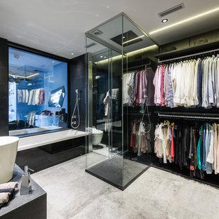 Immagine di uno spazio per vestirsi unisex minimal di medie dimensioni con nessun'anta, ante nere, pavimento in cemento e pavimento grigio