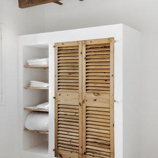 Inspiration för små medelhavsstil klädskåp för könsneutrala, med skåp i ljust trä, betonggolv och luckor med lamellpanel