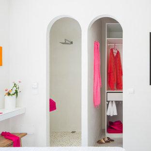 Imagen de armario vestidor mediterráneo, de tamaño medio, con suelo de baldosas de cerámica, suelo blanco, armarios abiertos y puertas de armario blancas