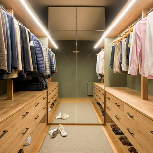 This is an example of a scandinavian gender-neutral dressing room in Barcelona with medium wood cabinets, medium hardwood floors, flat-panel cabinets and brown floor.