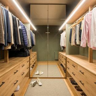 Neutrales Skandinavisches Ankleidezimmer mit Ankleidebereich, hellbraunen Holzschränken, braunem Holzboden, flächenbündigen Schrankfronten und braunem Boden in Barcelona